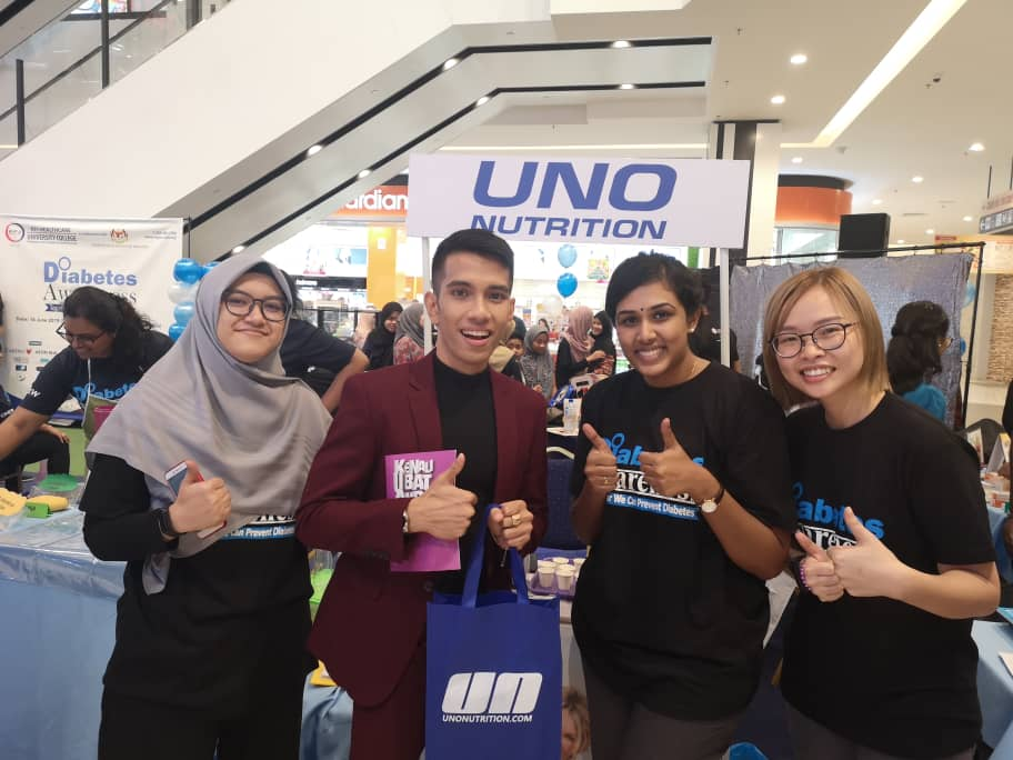 a picture of 4 people at a booth on a public health campaign. Uno staff taking picture with Naim Daniel a famous singer and actor.